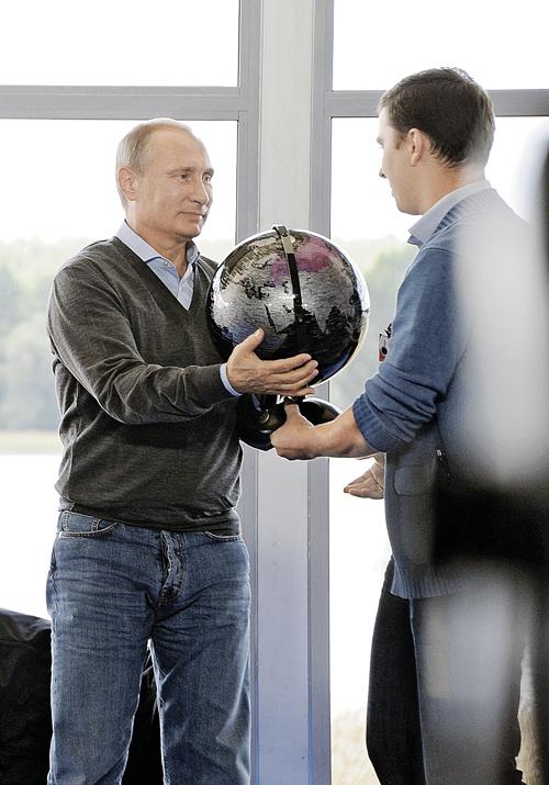 Участники молодежного форума «Селигер» засыпали президента вопросами о России и ситуации  в мире и подарили глобус - на память о встрече. Фото: РИА Новости