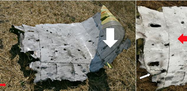 Кусок обшивки. И здесь прорывы металла разных размеров и формы. На обшивке закопчённость. Видно направление движения  следообразующих предметов. Показано стрелкой.