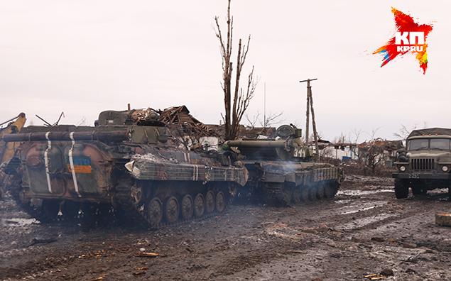 Мимо нас, рыча, проезжает танк, таща на тросе БМП с двумя белыми полосками на броне — отличительный знак ВСУ. Фото: Александр КОЦ, Дмитрий СТЕШИН