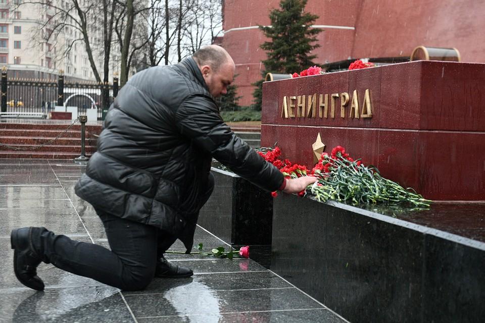 В память о жертвах террористического акта люди сегодня несут цветы