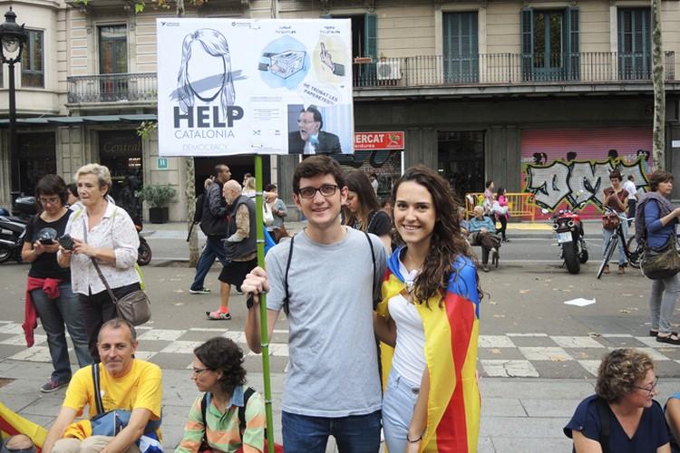 "Надпись на плакате: ""Помогите каталонской демократии""."