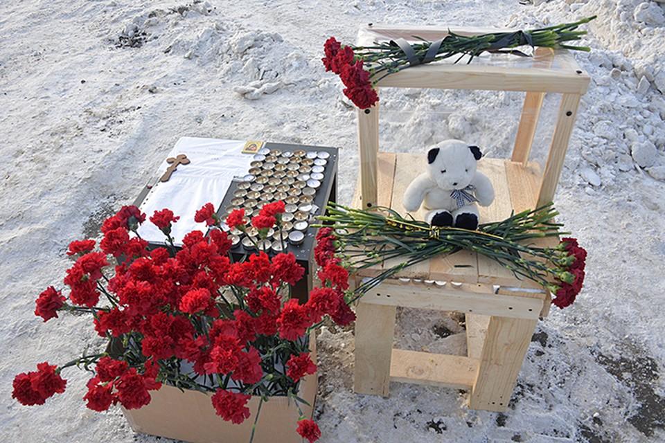 Жители села устроили стихийный мемориал. На столе горят свечи, лежат игрушки и много-много кроваво-красных гвоздик
