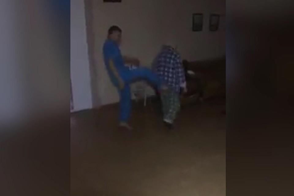 Кадр из видео: санитары глумятся над пожилым пациентом больницы.