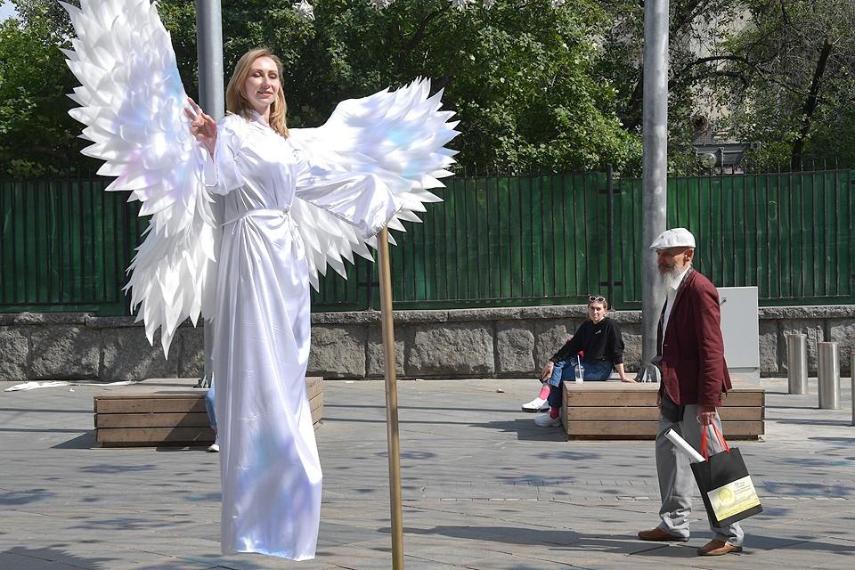 """Живая статуя """"Ангел"""" на Никольской улице в центре Москвы."""