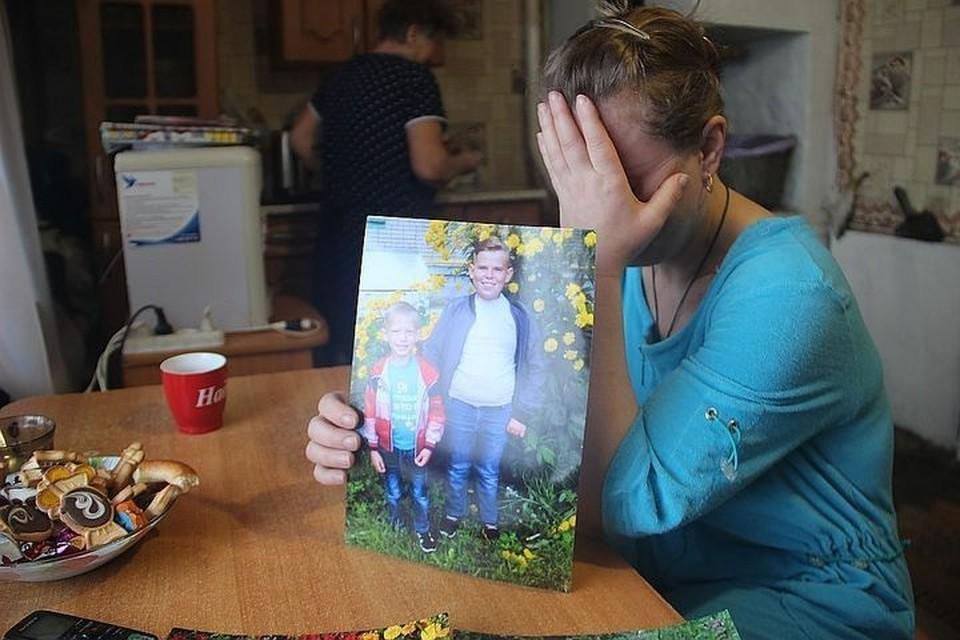Людмила Кузьмина показывает фотографию сыновей, которые погибли по вине коммунальщиков год назад.