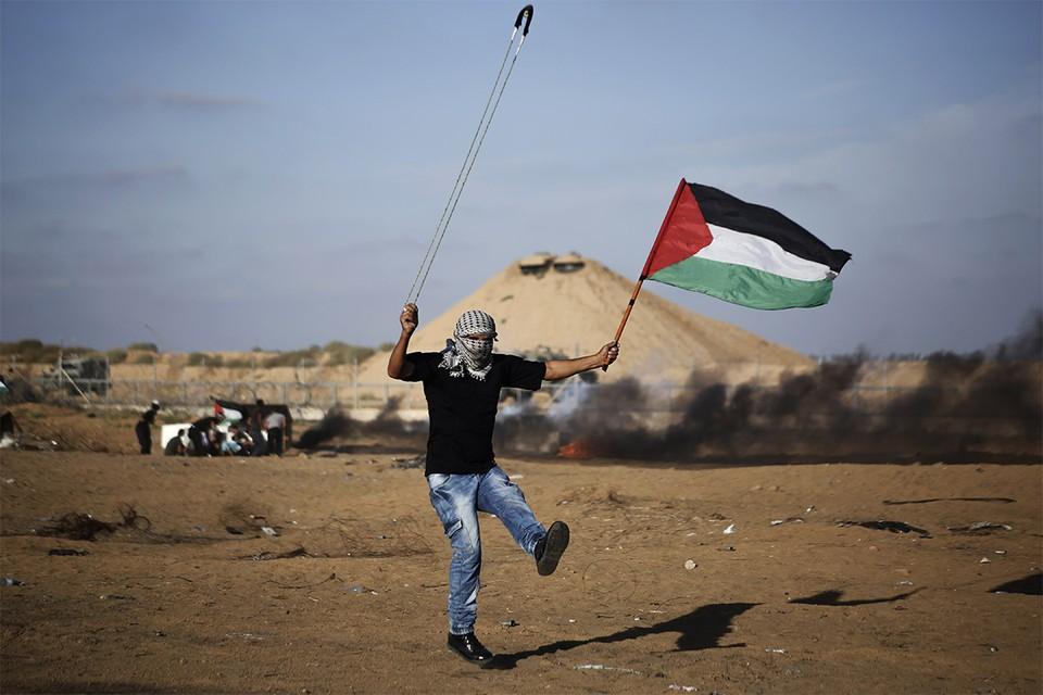 Палестинец выпускает камень из пращи в сторону израильских солдат.