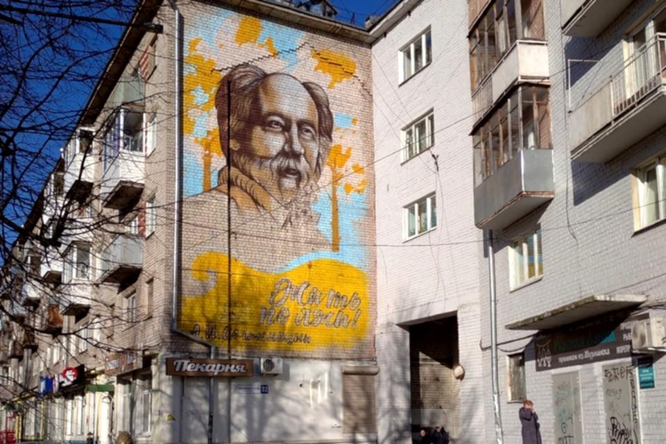 Недописанный портрет классика, изображенный на торце здания, цел, а вот весь смысл иллюстрации изменился полностью