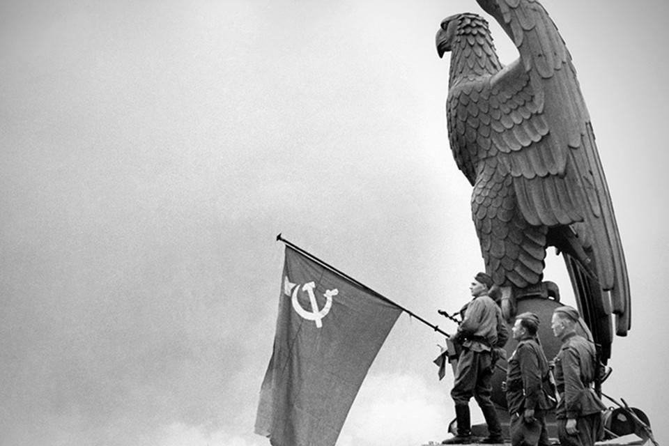 Бойцы Красной Армии вывешивают советский флаг над зданием аэропорта Темпельхоф, 1945 год.