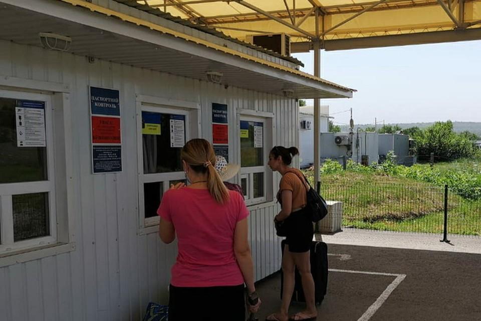 Украинские пограничники на КПВВ «Новотроицкое» проверяют предудущие въезды-выезды людей, которые проходят контроль. Фото ГПСУ