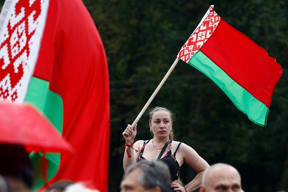 Участница митинга поддержки Александра Лукашенко с флагом.