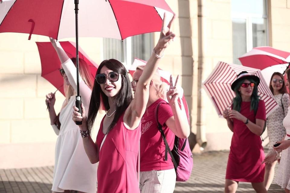 По Минску гуляют девушки с красно-белыми зонтиками.