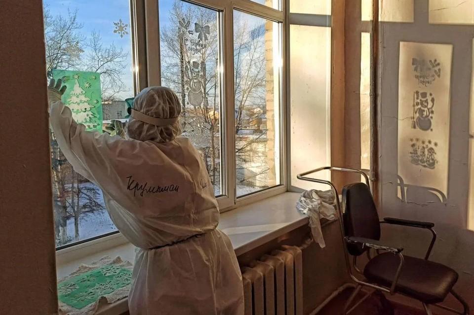 Фото дня - врач в защитном костюме украшает окна ковидного госпиталя. Фото: минздрав Челябинской области