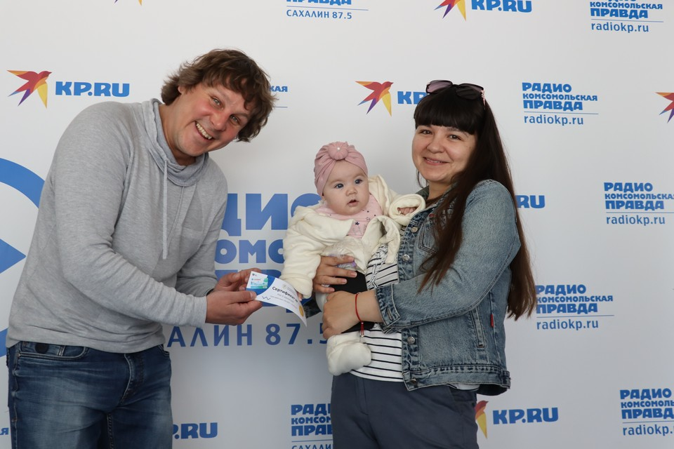 Ведущий радио «Комсомольская правда – Сахалин» Яков Морозов вручает приз одной из победительниц викторины