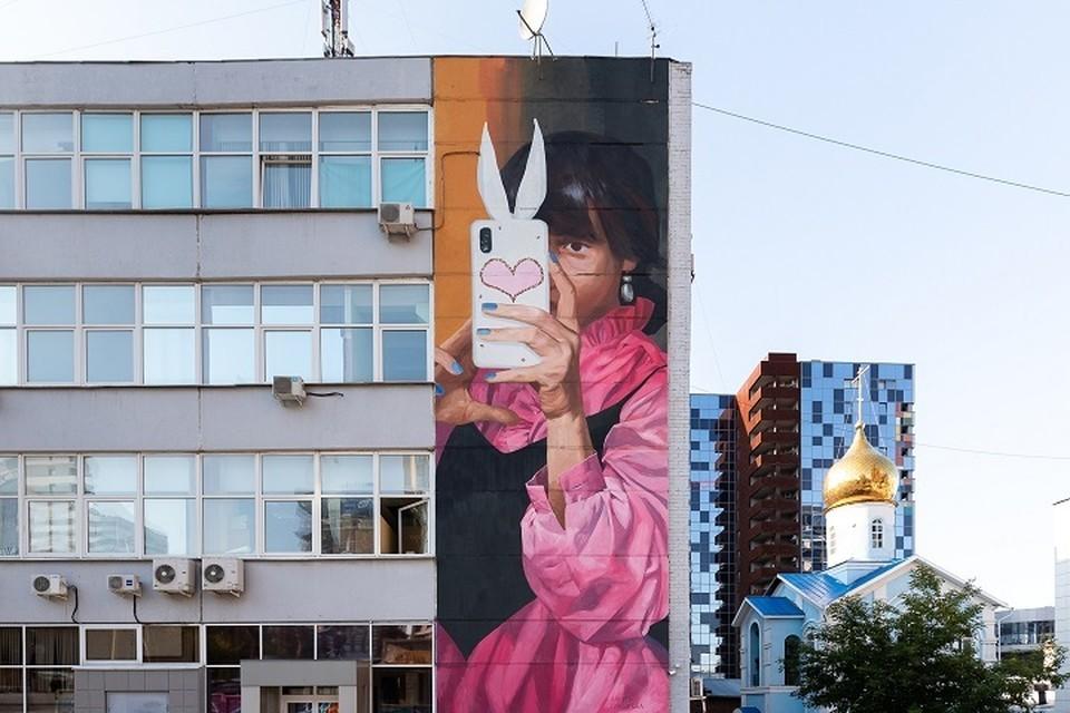 Анетта Лукьянова нарисовала стене офисного здания изображение девушки с телефоном. Фото: пресс-служба фестиваля «Стенограффия»