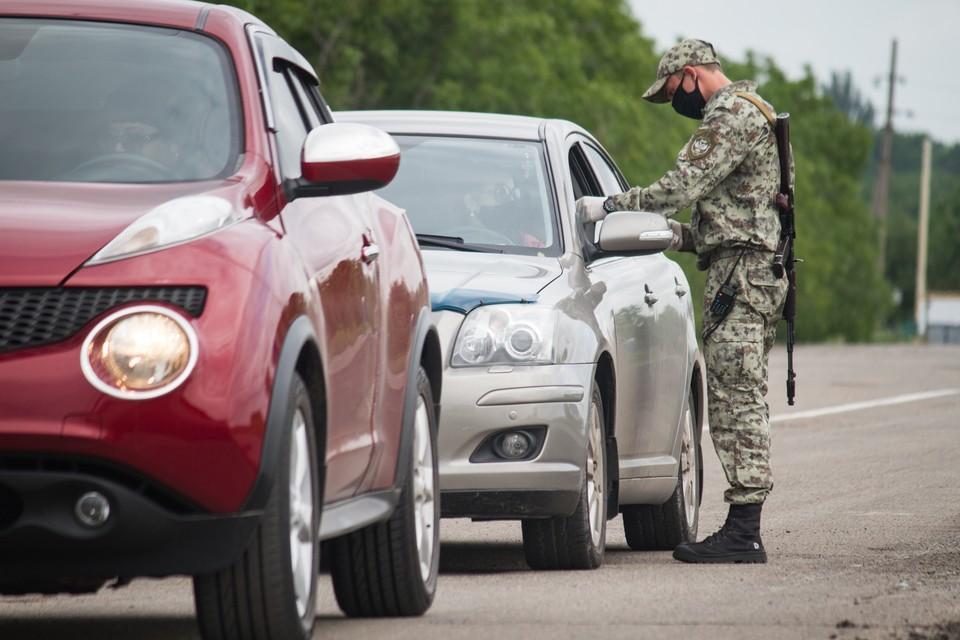 Боец сил обороны ДНР проверяет документы у водителя автомобиля, покидающего непризнанную республику.