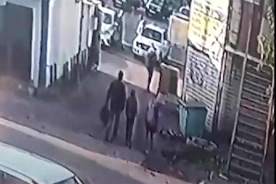 Подружки, выйдя из магазина в сопровождении неизвестного мужчины, вместе с ним скрылись за углом соседнего здания. Фото: кадр видео.