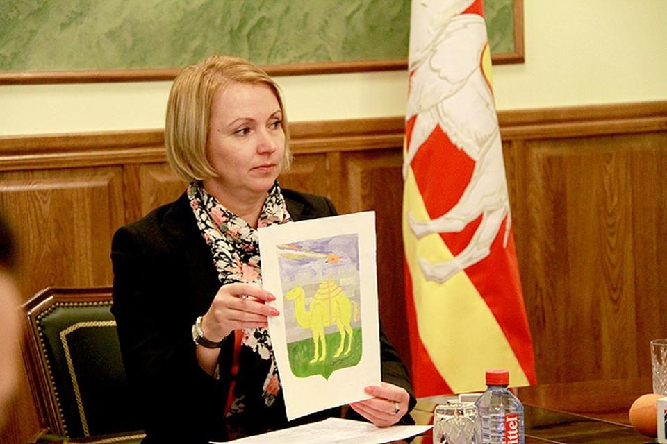 Ирина Гехт демонстрирует детский рисунок с новым гербом Челябинска