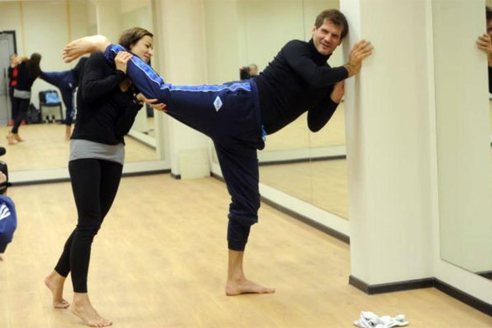 Фигуристка Маргарита Дробязко дает уроки растяжки своему партнеру- хоккеисту Алексею Яшину.
