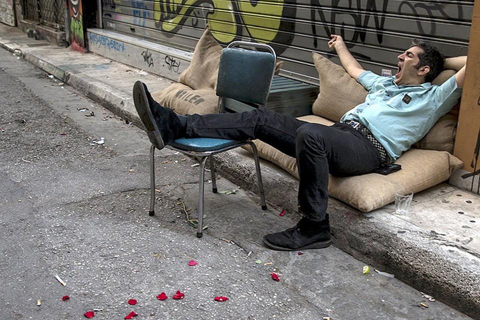 Житель Афин зевает в ожидании разрешения кризиса в отношениях кредиторов Евросоюза и греческих властей.