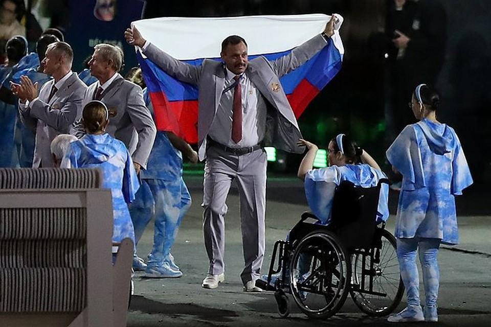 Член белорусской делегации достал российский флаг во время Парада наций. Фото: FA Bobo/PIXSELL/PA Images