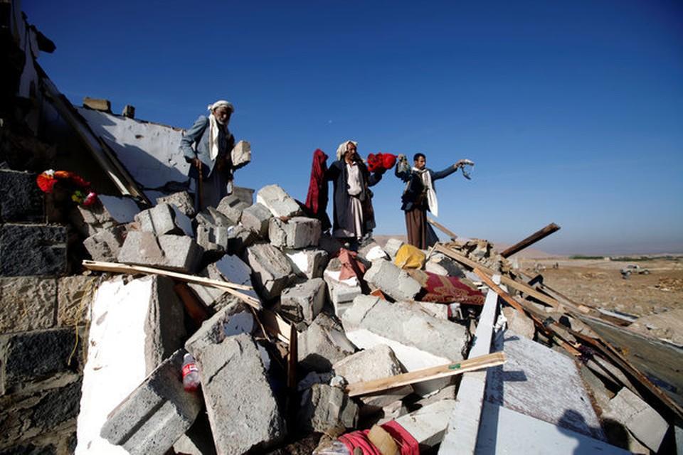 Женщины на месте авиаудара собирают одежду убитых