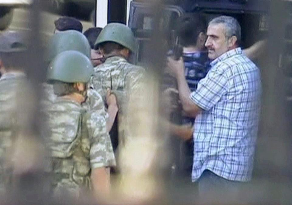 Блокировавшие мост через Босфор солдаты сдают оружие и отправляются в полицейский броневик.