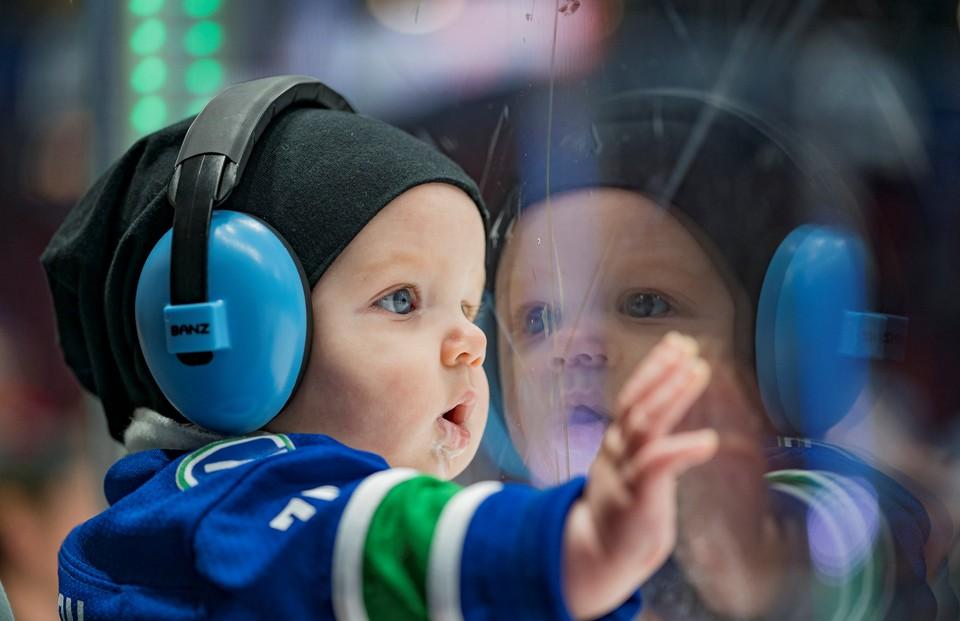 Юный болельщик наблюдает за игрой Национальной хоккейной лиги в Ванкувере.