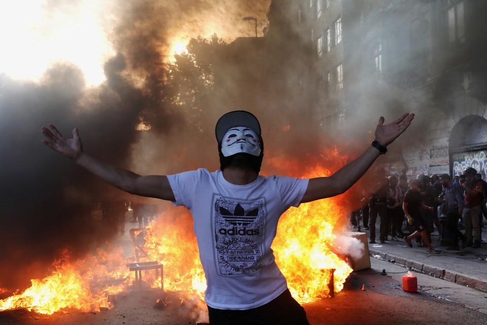 Участник уличных протестов в столице Чили на фоне горящей баррикады.