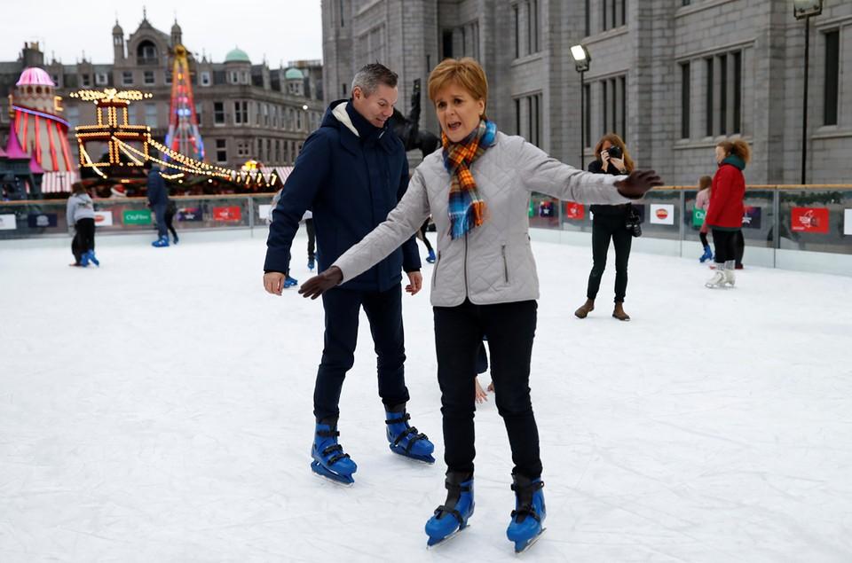 Премьер-министр Шотландии Никола Стерджен и министр финансов Шотландии Дерек Маккей катаются на коньках во время предвыборного мероприятия в Абердине.