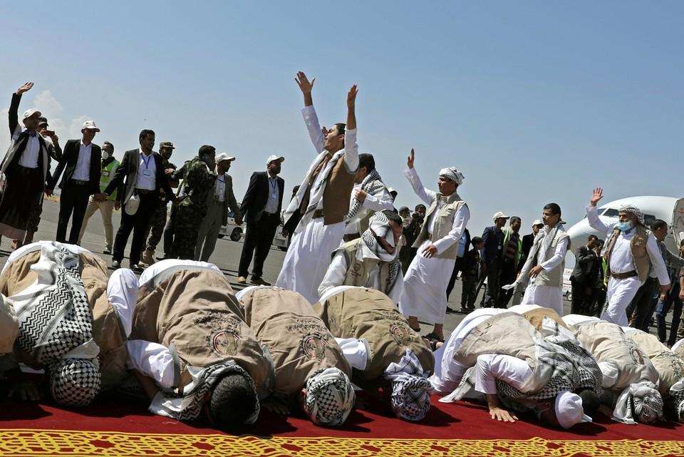 Возвращенные из плена хуситы целуют землю, спустившись по трапу самолета.