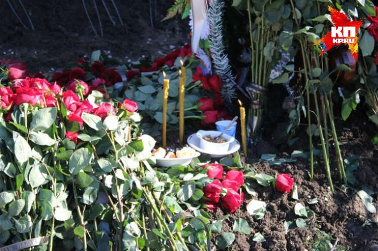 Посетители оставляют на могиле свечи и цветы.