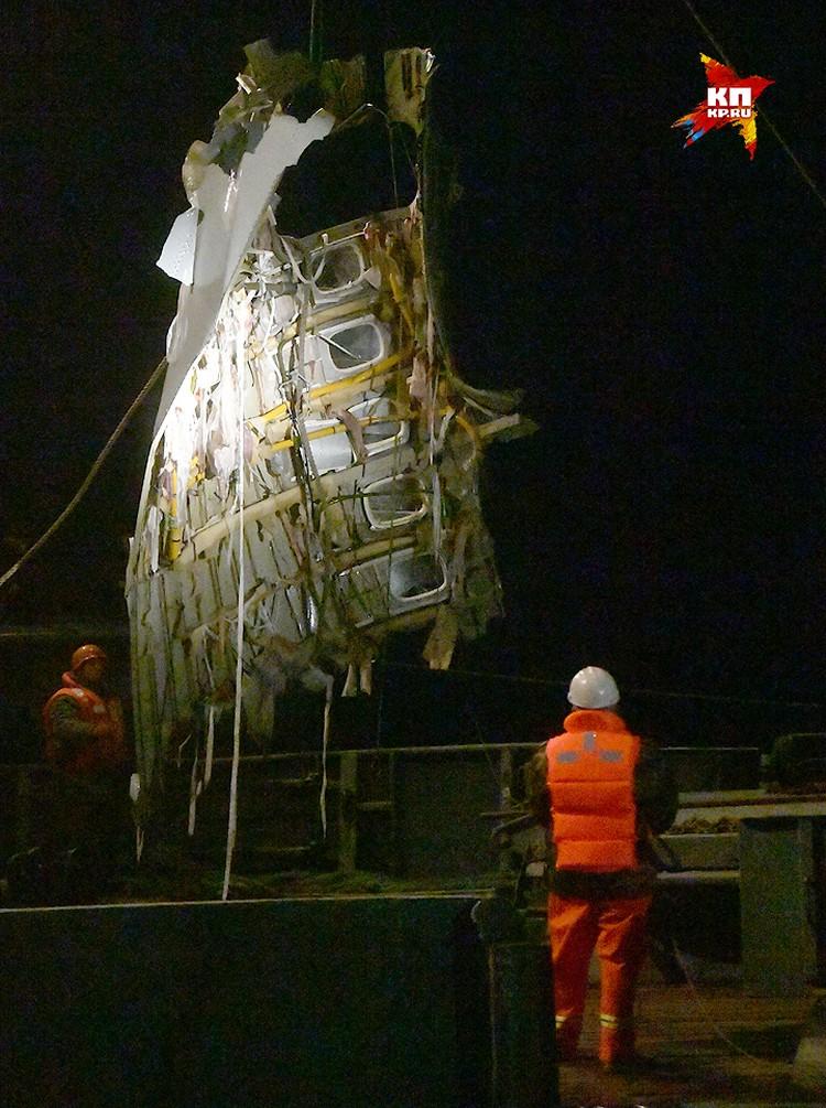 Обломок фюзеляжа Ту-154 выгружают на палубу судна спасателей.