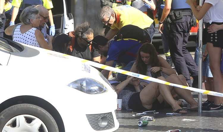 Пострадавшие от теракта лежат на земле, пока им оказывают медицинскую помощь.