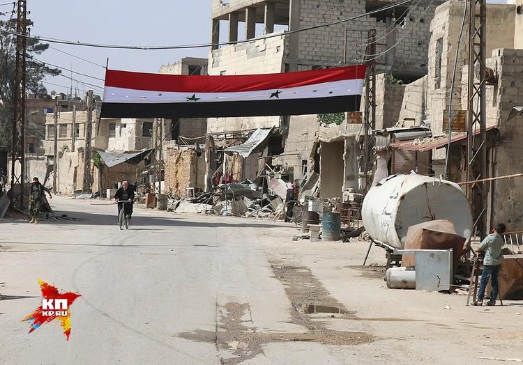 Растяжка с государственным флагом Сирии в районе, годами удерживаемом боевиками-джихадистами.