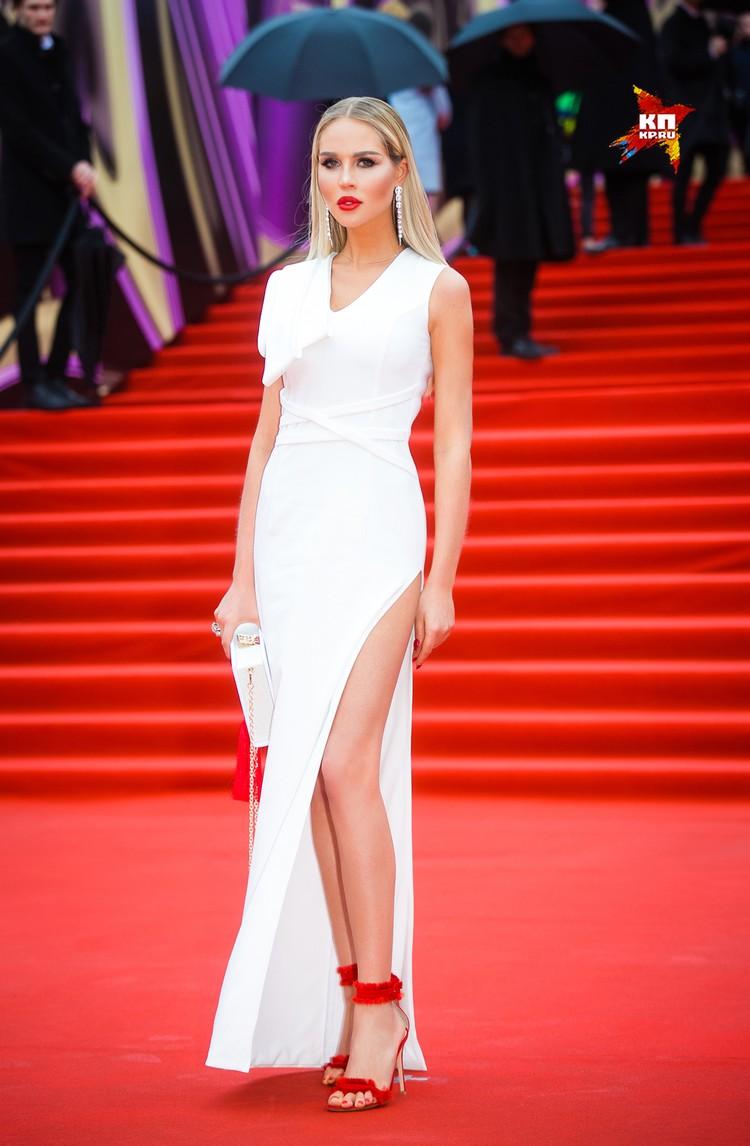 Жена футболиста Павла Погребняка Мария даже в дождь надела на дорожку лёгкое платье с высокими разрезами.