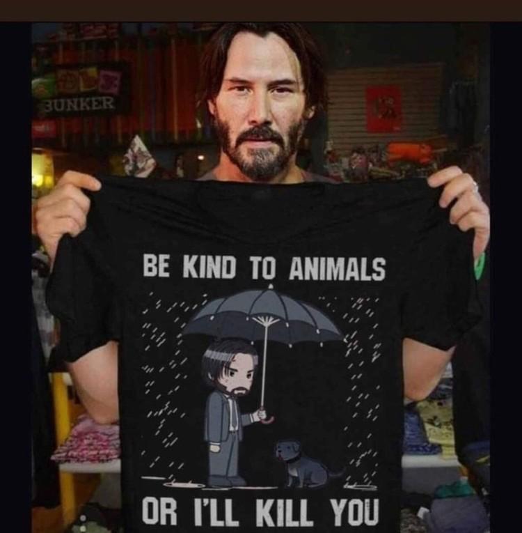 """Киану Ривз держит футболку с надписью """"Будьте добры к животным, или я убью вас"""""""