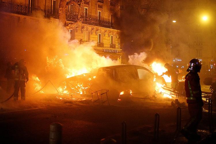 Пожарные тушат автомобили в ходе ночных беспорядков в Париже.