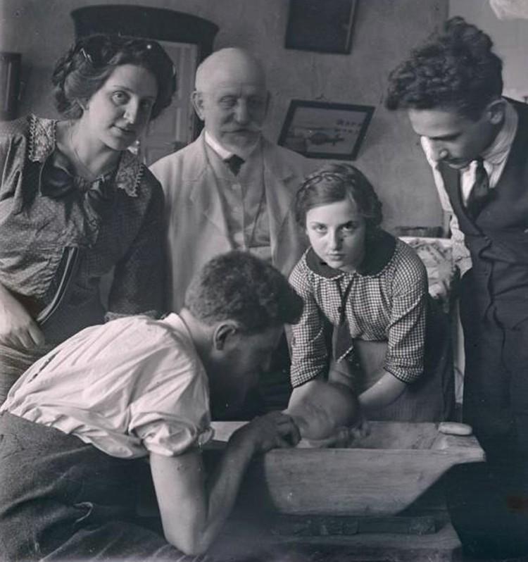 В городах тоже придерживались традиций – например, на этом фото из Гродно начала ХХ века вся семья присутствует при первом купании младенца в деревянной ванночке. Фото: russianphoto.ru