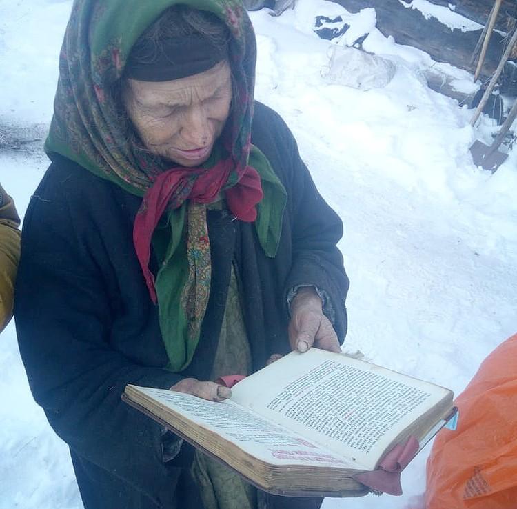Агафья Лыкова со старинной церковной книгой.