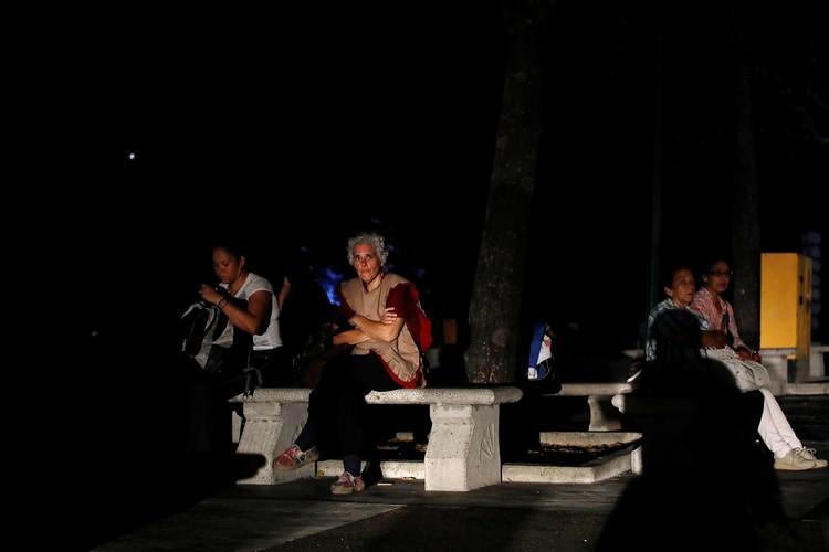 Люди в парках Каракаса во время отключения электричества в столице Венесуэлы.