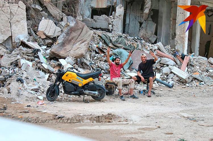 Разбитые дороги, рухнувшие плиты перекрытий жилых домов, ржавые расплющенные машины, стены, изъеденные свинцом - это тоже Бенгази