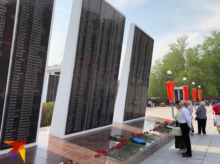 К мемориалу возлагают цветы и читают выгравированные имена павших