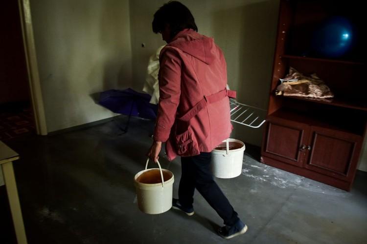 Воду из дома люди выносят ведрами.