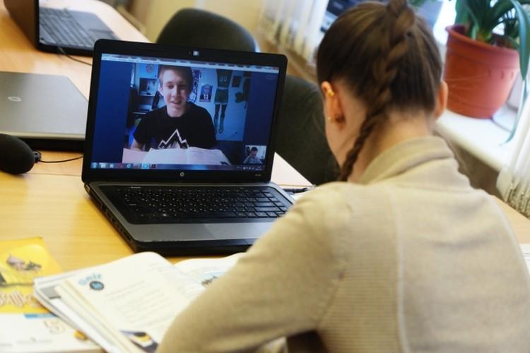 Молодой педагог занимается с учеником по скайпу