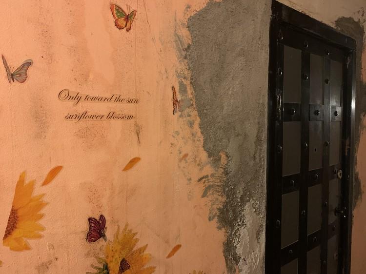 """Возле двери в квартиру убийцы нарисованы подсолнухи, бабочки и фраза """"только вперед, к солнцу. Цветение подсолнуха"""""""