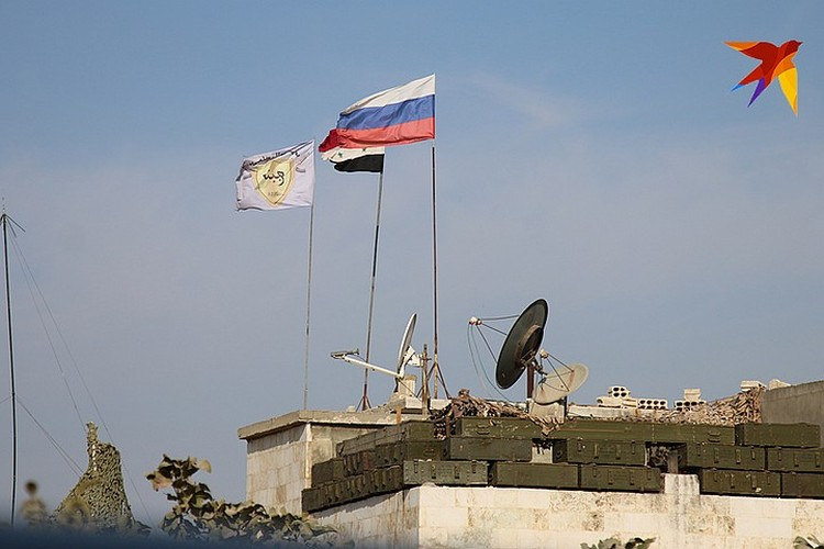 Курдский, сирийский и российские флаги над городом Кобани.
