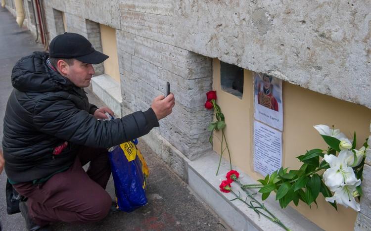 К импровизированному мемориалу на набережной реки Мойки люди уже несут цветы.