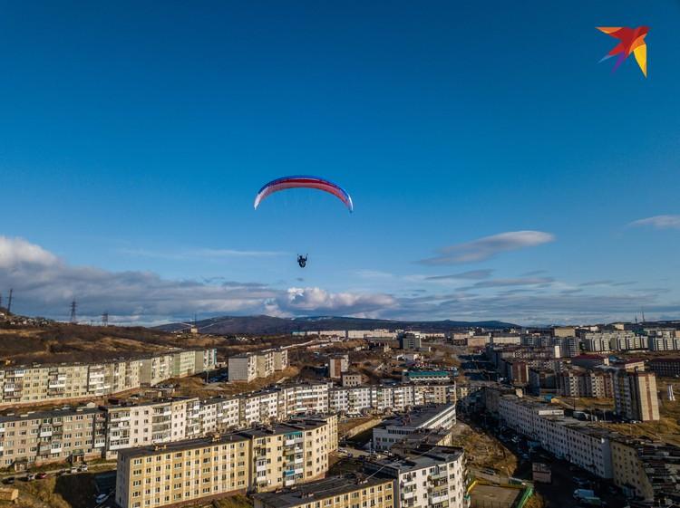 Парапланерист в солнечный день пролетает над Магаданом.