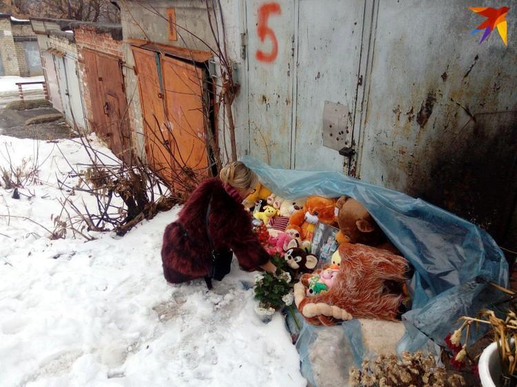 Мама убитой девочки возложила цветы к гаражу, где нашли тело ее дочери