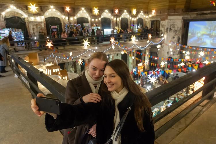 Петербуржцы активно фотографируются на красивом праздничном фоне.